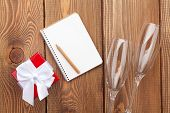 Blank notepad for copy space, valentines day gift box and two champagne glasses over wooden background