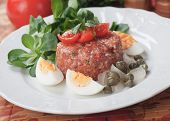 Tartar steak, raw ground beef meal with boiled eggs, capers and cherry tomato