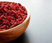 Wooden Bowl Full of Dried Goji Berries on the Dark Table. Healthy Diet