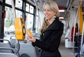 Woman validating electronic ticket in public transport