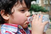A young boy drinking water