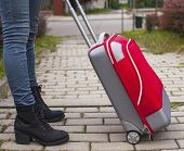 Young girl feet's in jeans with near a red travel suitcase.