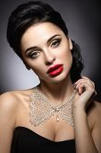 Beautiful woman with evening make-up, red lips and evening hairstyle. Beauty face.