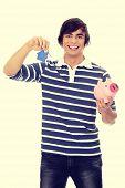 Young man with key and piggybank