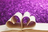 Pages of open book rolled in heart shape on glitter background