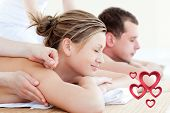 Loving couple having an acupunctre therapy against pink hearts