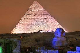stock photo of triangular pyramids  - CAIRO EGYPT - JANUARY 1 2009: Giza pyramid and Sphinx light up for magical sound and light show. ** Note: Visible grain at 100%, best at smaller sizes - JPG