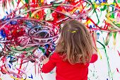 picture of wall painting  - Close up Young Blond Kid Painting Abstract Design Using Various Colors on White Wall During her Painting Time - JPG