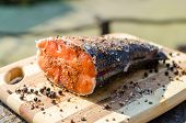 stock photo of fish  - Close up shot of prepared peace of fresh salmon fish outdoors on wooden chopping board rustic style of grilled fish - JPG