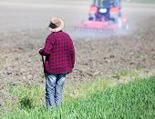 pic of hoe  - Rear view of farmer with hoe standing on fertile land and looking at tractor plowing soil - JPG