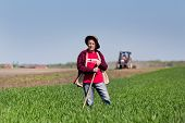 foto of hoe  - Senior peasant with hoe standing on farmland tractor in background - JPG