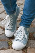 stock photo of paving stone  - woman retro tennis shoes and blue jeans with stone paving in background - JPG