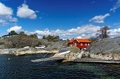 stock photo of puffy  - Red House fishing in the Gulf of spring. Spring view of the small bay in the south of Norway. Early spring puffy clouds over water ** Note: Soft Focus at 100%, best at smaller sizes - JPG