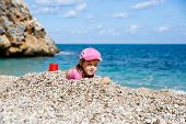 picture of children beach  - Girl buried in beach pebbles smiling and enjoying free time on the beach dressed in wetsuit and a hat for sun protection - JPG