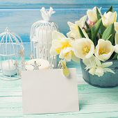 stock photo of daffodils  - Bright white daffodils and tulips flowers in bucket candles and empty tag on turquoise painted wooden planks againsy blue wall - JPG