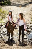 stock photo of horse-riders  - cute female kid jockey having fun learning riding pony outdoors happy with young Australian American horse instructor woman in cowboy look teaching the little rider in summer nature countryside - JPG