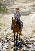 foto of horse-riders  - young horse instructor or cattleman riding the animal wearing sunglasses cowboy hat and rider boots looking cool while taking a ride at countryside summer landscape