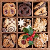 stock photo of holly  - Assorted Christmas cookies in wooden box with holly sprig - JPG