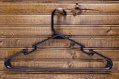 stock photo of clothes hanger  - Black clothes hanger on a wooden wall - JPG