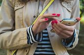 stock photo of jacket  - The girl uses the phone close up she is dressed in a beige jacket and striped shirt at the shoulder yellow strap from the bag - JPG