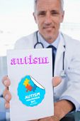 stock photo of prescription pad  - The word autism and portrait of a male doctor showing a blank prescription sheet against autism awareness day - JPG