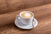 picture of generous  - White cup of delicious aromatic freshly prepared cappuccino with generous portion of soft cream on a rustic wooden table - JPG