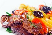 picture of stew  - Stewed mutton with potatoes and black plums on a white plate - JPG