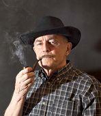 stock photo of hillbilly  - Cowboy in black hat smoking a pipe - JPG