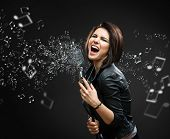 Постер, плакат: Female rock musician holding sounding mike with melody in the air on grey background
