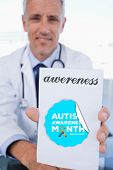 image of prescription pad  - The word awereness and portrait of a male doctor showing a blank prescription sheet against autism awareness month - JPG
