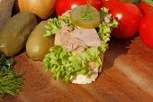 image of baguette  - Slice of baguette with tuna fillet garnished with lettuce onion tomato and pickles on a wooden board - JPG