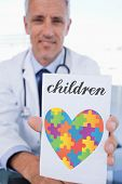 stock photo of prescription pad  - The word children and portrait of a male doctor showing a blank prescription sheet against autism awareness heart - JPG