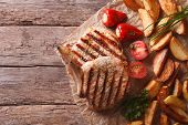 stock photo of roasted pork  - Grilled pork steak with potatoes and vegetables on paper - JPG