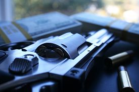 image of smuggling  - Money and guns stock photo close up - JPG