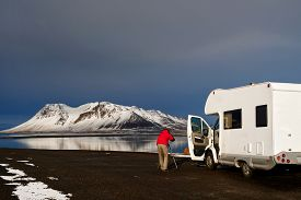 stock photo of camper  - Photographer taking photos of beautiful Icelandic landscape outside mobile motor home RV camper van traveling through Iceland - JPG