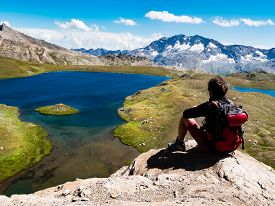 image of italian alps  - Trekker takes a rest looking at mountain panorama - JPG