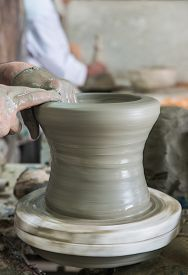 picture of pottery  - The artist mold the pottery on the circulated plate in pottery factory name Serghini Maitre Potier et Zellige Fassi in Fes Morocco - JPG