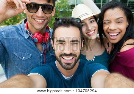 Closeup shot of young friends take a selfie. Happy smiling girls and guys photographing self. Laughi