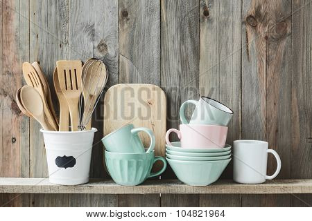 Kitchen cooking utensils in ceramic storage pot on a shelf on a rustic wooden wall