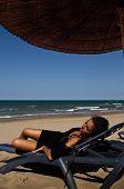 Girl in black dress relaxing on the beach