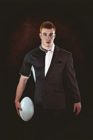 stock photo of half-dressed  - Rugby player holding a rugby ball against half a suit - JPG