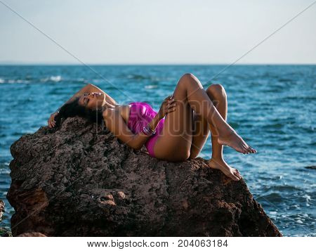poster of Portrait of cheerful black people, pretty happy young afro american woman smiling on sea beach. Sexy girl in pink swimsuit and jewelry enjoying nature.Lady wearing bikini.