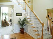 stock photo of front-entry  - A foyer in a modern american home with a carpeted staircase a view of the family room and a prominent Welcome sign  - JPG