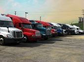 stock photo of 18-wheeler  - trucks truckstop stop rest trucking 18 wheeler transportation cross country drive driving driver CDL sky big road - JPG