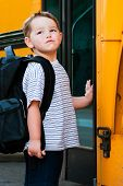 Defiant young boy in front of yellow school bus waiting to board on first day back to school.