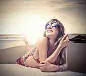 stock photo of beautiful woman face  - Smiling beautiful woman in bikini lying on a beach - JPG