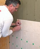 Man installs ceramic tile in bathroom shower