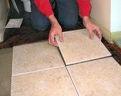 Hands installing ceramic tile
