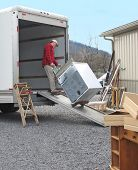 Man pulls dryer onto moving van using a dolly