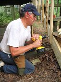Carpenter uses screw gun to rebuild stairs to deck